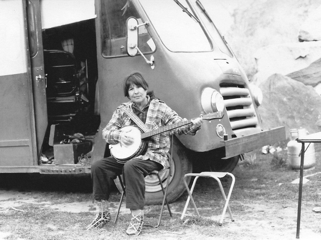 image of Frances playing her banjo, Cleo-May, outside Emma the camper