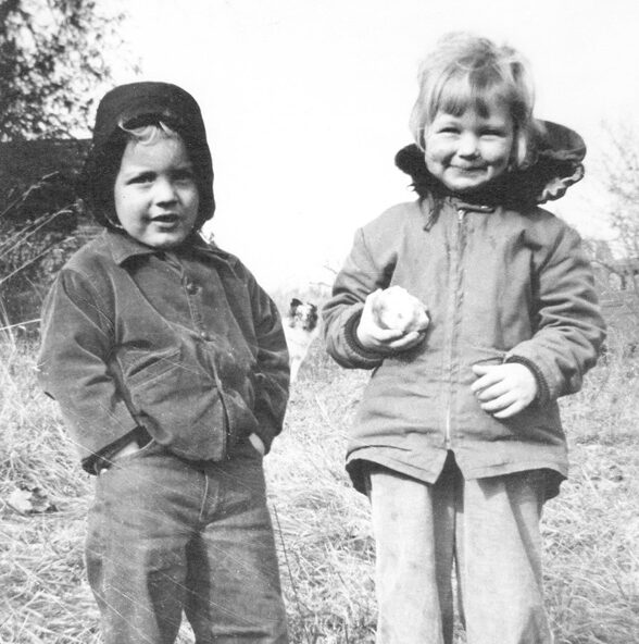 Little boy with hands in pockets and little girl holding a partly eaten apple