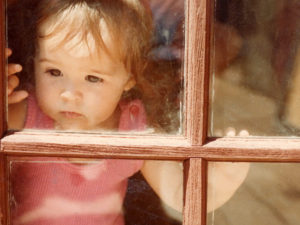 Little girl looks seriously through one of four window panes